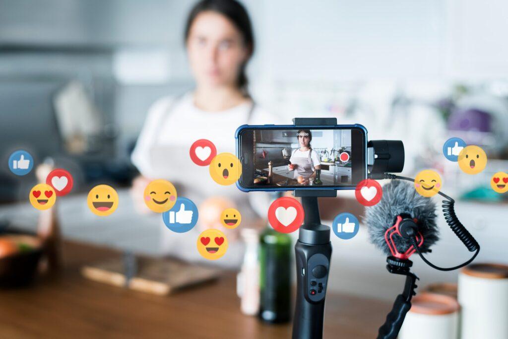 Influenceuse cuisine derrière caméra avec des pictos emojis flottants