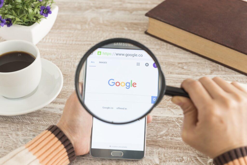 Homme regardant à la loupe le moteur de recherche Google