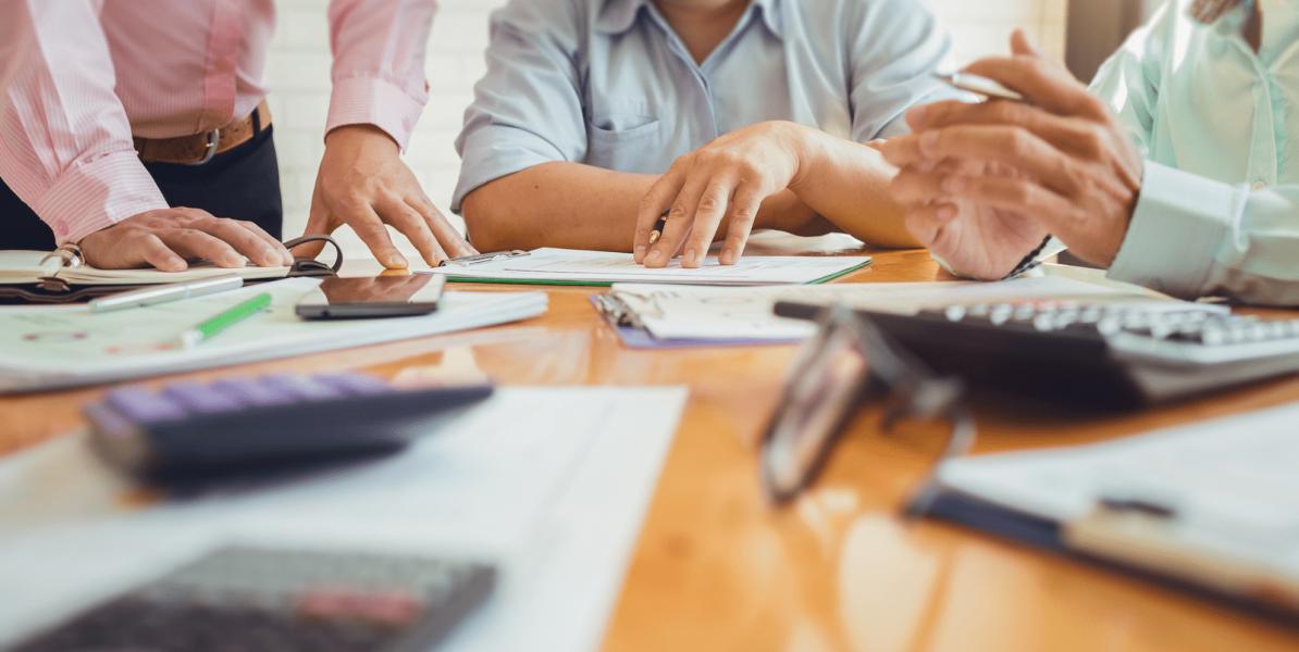 collaborateurs regroupés autour d'une table prenant des décisions financières