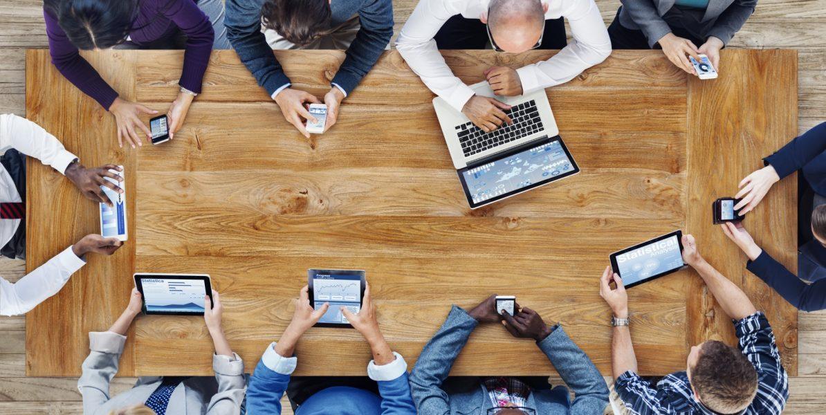 Professionnels autour d'une table manipulant divers outils numériques (ordinateur, tablette, mobile)